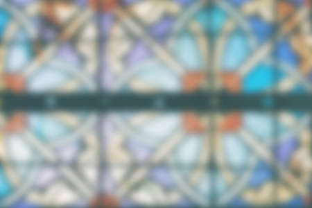 Blurred Image of a multicolored stained glass window. Stained glass in a cathedral with irregular block pattern