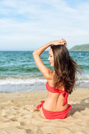 Relaxed girl enjoying tropical beach. Young beautiful Brunette woman in red bikini sitting on beach. Clear blue water, yellow dry sand. Back view Stock Photo