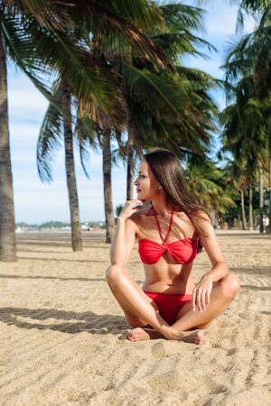 humility: Relaxed girl enjoying tropical beach. Young beautiful Brunette woman in red bikini practicing morning or evening meditation in nature at the beach Stock Photo