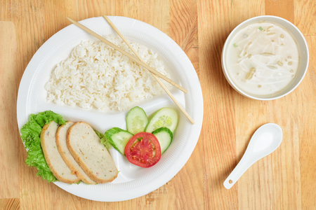 school cafeteria: Disposable plastic food plate on wooden table. White plate with rice, meat and vegetables. Soup with sprouts. Spoon and bamboo chopsticks. Healthy take-away concept