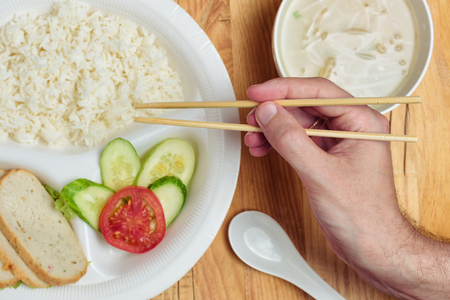 Disposable plastic food plate on wooden table. White plate with rice, meat and vegetables. Soup with sprouts. Mans hand holding bamboo chopsticks. Healthy take-away concept. Stock Photo