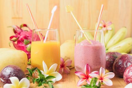 Mangue, banane et fraise secoue sur une table en bois clair. Dragon, fruit de la passion et fleurs de frangipanier sur fond Banque d'images - 77971570