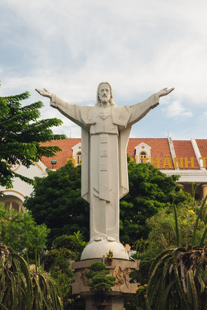 popular: Grey statue with open arms in the courtyard of Tan Dinh Pink Catholic Church. Ho Chi Minh city, Vietnam, may 2017
