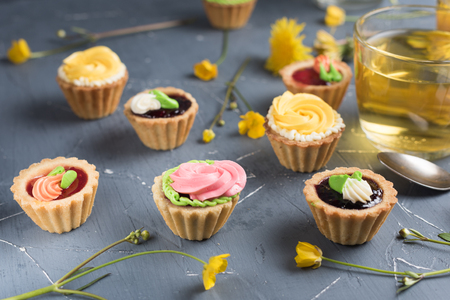 Colorful cupcakes on a gray plate and table. Cakes with cream and jam. Cup of green tea and yellow flowers on a background
