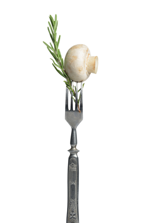 marinade: Common mushroom on a vintage fork. Champignon and rosemary on the stainless steel fork isolated on a white background