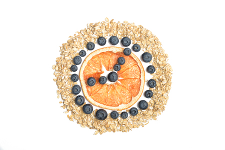 Tropical abstract background whith rolled oats like a clock. Berries on the white background.