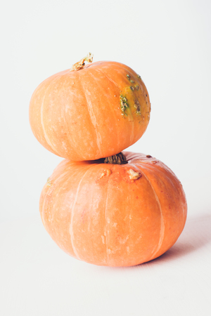 Two stacked mini pumpkins on a gray background. Studio shot of orange pumpkins on a wooden table