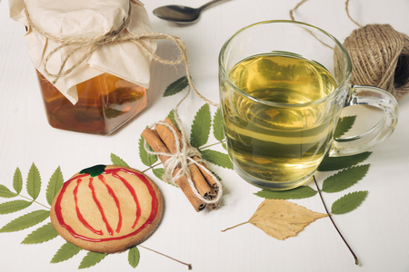 Homemade sugar cookies with honey. Glass of hot drink on white wooden table. Fall concept. Cookie pumpkin