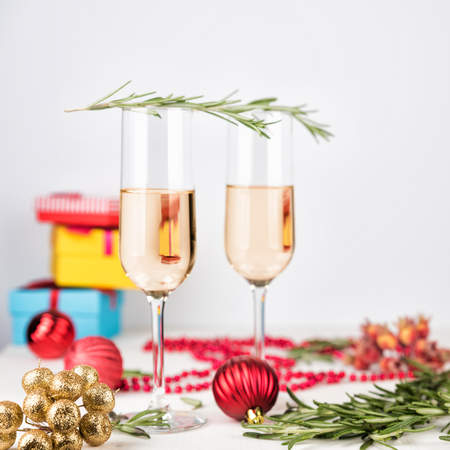 Two champagne glasses on light bokeh background. New Year and Christmas Celebration. Red baubles, berries, garland, tree ornaments, rosemary branch and gift boxes