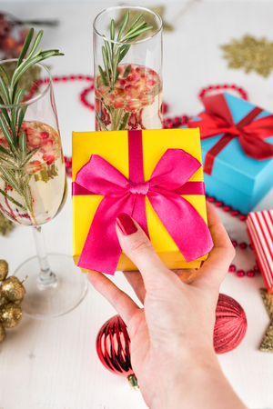 New Year and Christmas Celebration. Champagne glasses on background. Red baubles, berries, garland, tree ornaments. Woman hand with manicure holding gift boxes Stock Photo