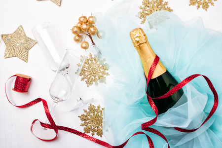 Bottle of a champagne and glasses. Celebration Flat lay. White wooden background, turquoise tulle, golden berries and snowflake, red ribbon, tree decoration Stock Photo