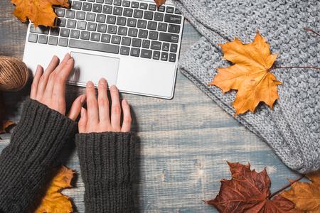 Arbeitsbereich mit gelben und roten Ahornblättern. Desktop mit Laptop, gefallene Blätter auf grauem hölzernem Hintergrund. Flache Lage, Draufsicht. Frau übergibt das Schreiben