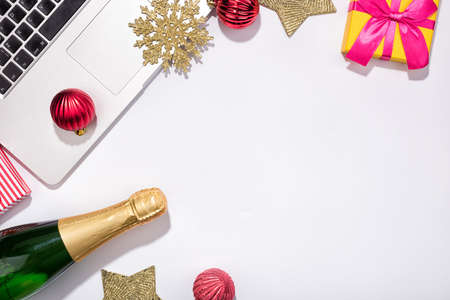 Workspace with Red baubles and tree branches. Christmas holidays composition with bottle of champagne on white background with copy space for your text