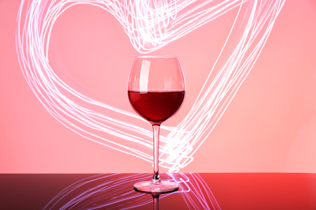 Glass of red wine on neon glow. Silhouette of glass on pink and claret background. Heart, Valentine day