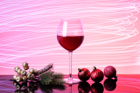 Glass of red wine on neon glow. Silhouette of glass on pink and claret background. Golden berries. Red baubles, green fir-tree branch