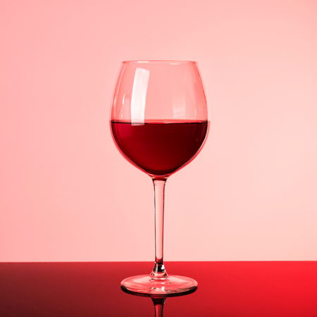 Glass of red wine on neon glow. Silhouette of glass on pink and claret background. Stock Photo