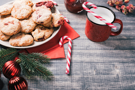 Traditional British dessert, scones with strawberries. Sweet coconut cookies with raspberry jam and yogurt on wooden table. Candy cane, fir-tree branches, baubles Stok Fotoğraf