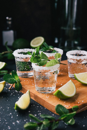 Alcohol shots on wooden tray. Shooter glasses of vodka or Tequila on black table. Mojito with mint