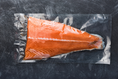 Salmon fillet packaged in plastic vacuum pack. Fresh fish in packing sell in supermarket. Metal black background