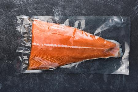 Filetto di salmone confezionato in busta sottovuoto di plastica. Pesce fresco nella vendita dell'imballaggio in supermercato. Sfondo nero metallico