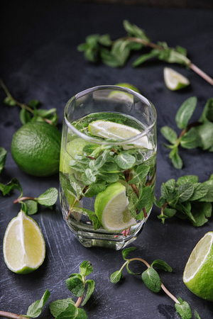 Glasse of Mojito with lime and mint. Summer refreshing cocktail on a gray metal background