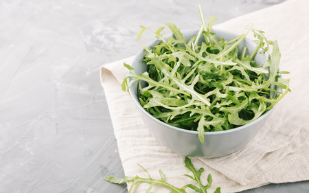 Fresh green arugula on a stone background. Garden rocket salad in a bowl on a gray table.
