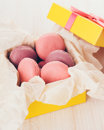 French macaroons in a box. Sweet cakes in a yellow box on a wooden table