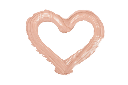 Close up of a make up liquid foundation heart shape isolated on white background.