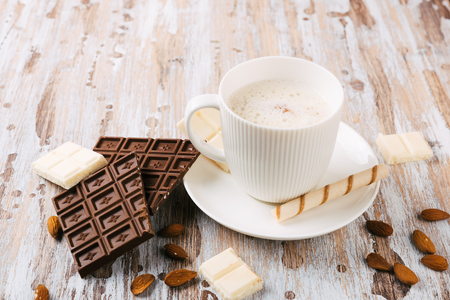 Cup of hot cocoa or Cappuccino or latte coffee with chocolate bar, almonds and whipped cream on wooden table