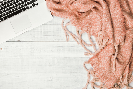 Home office desktop with a laptop, cozy warm pink plaid. Wooden white table, flat lay. Winter or autumn background, top view Reklamní fotografie