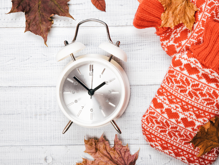 The vintage alarm clock and autumn fallen maple leaves and red hot-water bottle on the white wooden table background, flat Lay, top view. Copy space for your text
