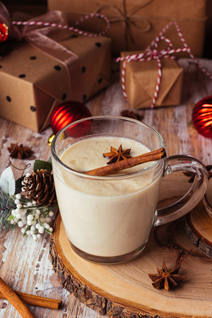 Traditional Christmas drink eggnog with cinnamon, anise stars and grated nutmeg in a glass mug on the wooden table. Gingerbreads, gift boxes, and fir-tree decoration