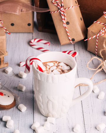 Cup of cocoa or chocolate on wooden Christmas background. Winter hot chocolate drink with marshmallows, snowman and a fir-tree cookies, candy canes Imagens
