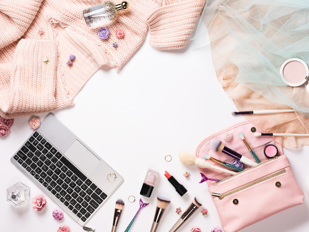 Home female workspace with a pink cardigan, laptop keyboard, dress, a makeup bag, brushes and cosmetics on white