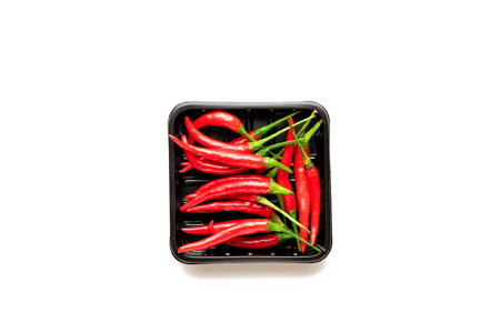 Fresh Red chili pepper in a black disposable plastic packing box isolated on a white background. Top view, flat lay Image Imagens