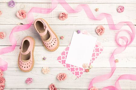 Summer Pink Baby girl shoes and card It is a girl in an envelope, and roses, ribbon on wooden background. Top view trendy leather sandal, flat lay. Copy space for your text