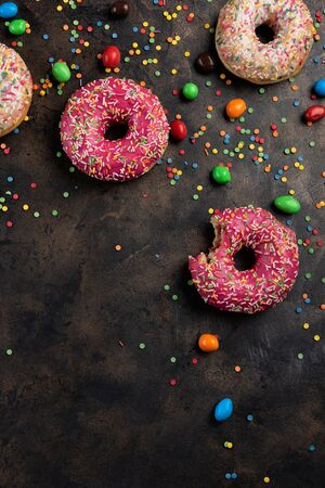 Different types of donuts with color candies beans on a fire-warm old metal background. Flatlay with copy space for your text Stockfoto