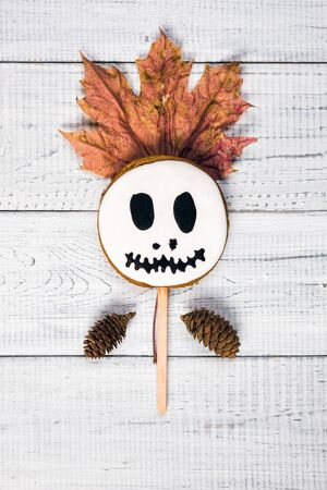 Funny delicious ginger cookies for Halloween on the wooden table. Cake pops like ghost and pumpkin, top view, flat lay