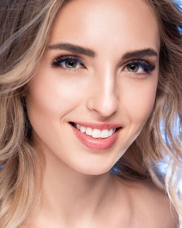 Beautiful blonde young woman with clean healthy skin. Girl facial treatment. Cosmetology, beauty and spa Banco de Imagens