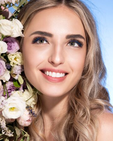 Beautiful blonde young woman with clean healthy skin on a face. Girl facial treatment. Bouquet of roses and other flowers