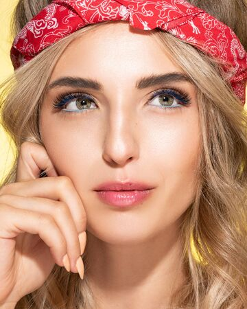 Beautiful blonde young woman with clean healthy skin on a face. Girl facial treatment. Red bandana on had