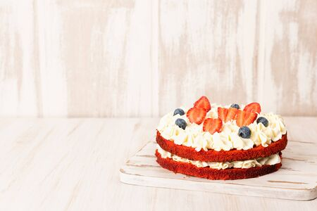 Red velvet cake with white cream and fruit and berries decoration on wooden table 스톡 콘텐츠