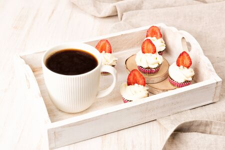 Cupcake with white cream and fruit and berries decoration on wooden table. Cup of coffee on a wooden tray