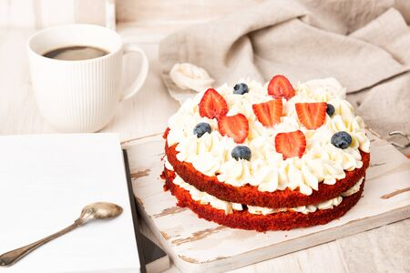 Red velvet cake with white cream and fruit and berries decoration on wooden table. Read a book and drink a coffe