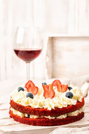 Red velvet cake with white cream and fruit and berries decoration on wooden table. Drink a glass of wine