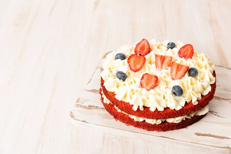 Red velvet cake with white cream and fruit and berries decoration on wooden table Stock fotó