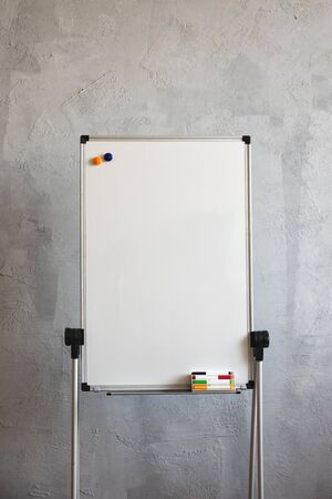 Big white board markers on grey background.  Writing board stands on the old dirty floor in the office.