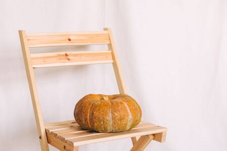 Pumpkin on a wooden stool, fabric background 写真素材