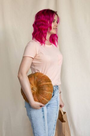 Young woman with pinh hair in blue jeans and pink t-shirt holding a big pumpkin Stock Photo