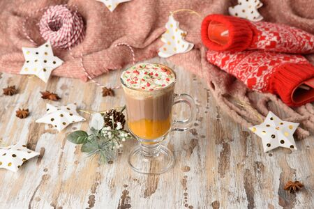 Pumpkin spice latte. Sweet chocolate hot drink with whipped cream on top on a wooden background. Copy space for your text